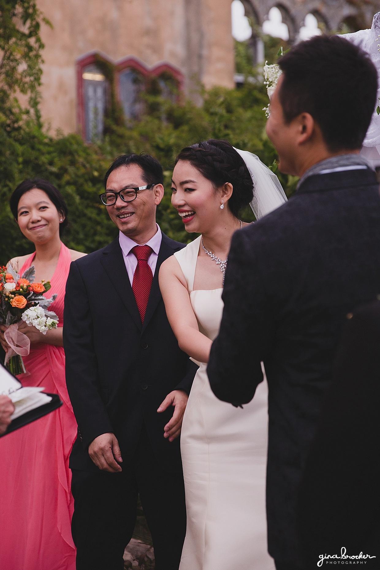 The bride smiles during her outdoor wedding ceremony in Hammond Castle